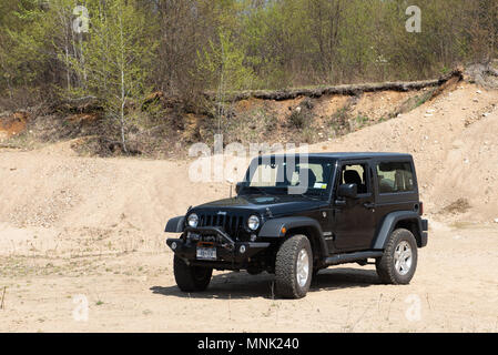 A 2016 black Jeep Wrangler Sport parked in a sand and gravel pit in the Adirondack Mountains, NY USA - Stock Image