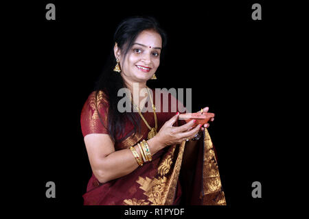 A middleaged Indian woman holding a traditional earthen lamp during Diwali festival in India, on black studio background. - Stock Image