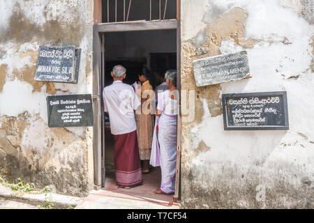 Kandy, Sri Lanka - March 14th 2011: People queuing in an attorneys office. Law offices are concentrated in a  particular street. - Stock Image