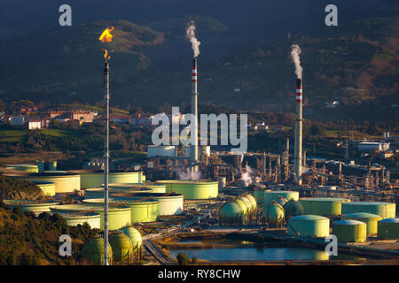 industrial refinery and storage tanks with smokestack and smoke - Stock Image