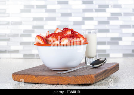 Sliced fresh strawberries in a vintage white metal bowl. - Stock Image