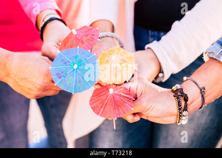 Closeup with group of people holding and showing four cocktail umbrellas together - friendship and team cooperation celebrating concept lifestyle - Stock Image