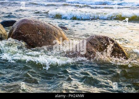 Waves crashing against stones - Stock Image