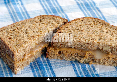 Peanut butter and honey sandwich on whole grain bread cut in two on a blue and white cloth. - Stock Image