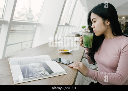 Young asiatic look girl drink green fresh tea and enjoy her life - Stock Image