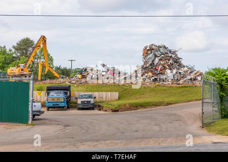 HICKORY, NC, USA-5/3/19: A Recycling center showing a large pile of metal scrap, and cranes moving the scrap. - Stock Image