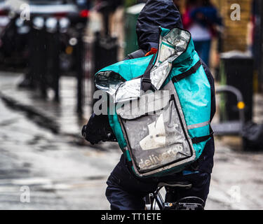 Deliveroo Courier in heavy rain in London - a Deliveroo Food Delivery Courier getting drenched in a heavy downpour - Stock Image