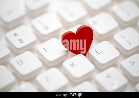 Small red heart on computer keyboard. Internet dating concept. - Stock Image