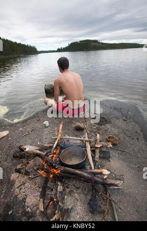 Man sitting next to a camping fire, countryside of northern Sweden. - Stock Image