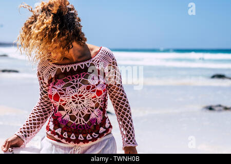 Beautiful woman with hand made dress enjoy the beach in summer vacation - outdoor leisre activity in tropical place - blue ocean and sky in background - Stock Image