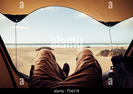 Alternative vacation concept with man in trekking clothes laying outside the tent campiing free at the beach looking the ocean horizon and enjoying th - Stock Image