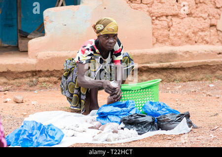 Adzopé, côte d'ivoire - June 10, 2017: a woman seated on a stool, her head tied by a scarf, before her a green basket  and black and blue bags, attach - Stock Image