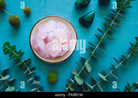 Rose Quartz with Malachite and Eucalyptus on Turquoise Table - Stock Image