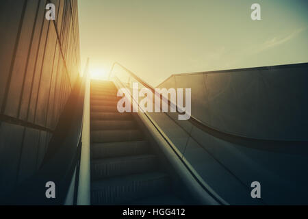 Outdoor city escalator stairway, under evening sun, with tiled wall on the left, view from bottom, vintage color - Stock Image