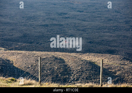 Marsden, UK. 27th Feb, 2019. Scorched moorland was still smouldering this afternoon following the dramatic fire overnight at Marsden Moor, near Saddleworth Moor. Firemen were using a special buggy to survey areas of ground still smouldering. Credit: James Copeland/Alamy Live News - Stock Image