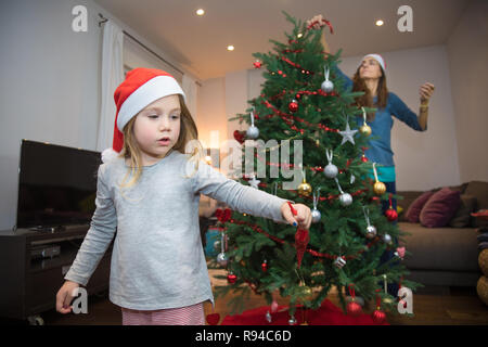 four years blonde cute girl with red Santa Claus hat and mother decorating Christmas tree at home - Stock Image