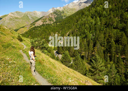 Female hiker in GR-11 footpath near Cinqueta de Añes Cruces river with Posets massif at the back (Viadós, Chistau valley,Huesca,Pyrenees,Aragon,Spain) - Stock Image