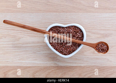 Alternative health care and dieting flax seeds in wooden spoon set up on rustic wooden background. - Stock Image