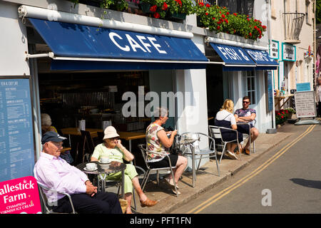 UK, Cornwall, Padstow, The Strand, visitors sat in sunshine outside waterfront Fish and Chip shop - Stock Image