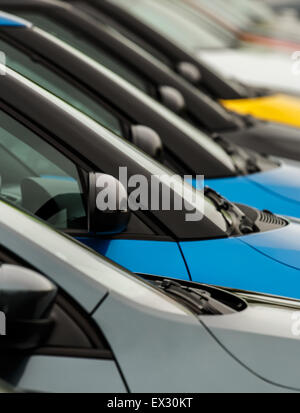 Vehicles for sale parked in a row with close up detail on the wing mirror without focus on any particular model - Stock Image