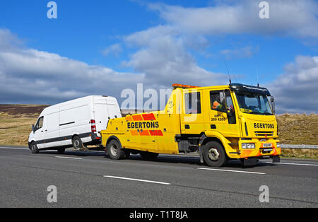 Edgertons Recovery HGV with White Van. M6 Motorway, Southbound, Shap, Cumbria, England, United Kingdom, Europe. - Stock Image