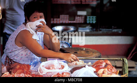 A Filipina woman selling meat at a local market in Manila, the Philippines. - Stock Image