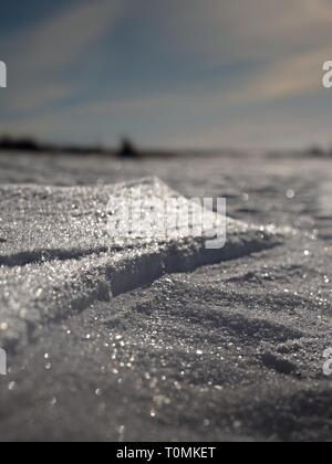 Real winter background. Frosty shinning field in strong morning sun. - Stock Image