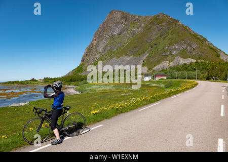 Female cyclist in Gimsoya, Lofoten Islands, Norway. - Stock Image