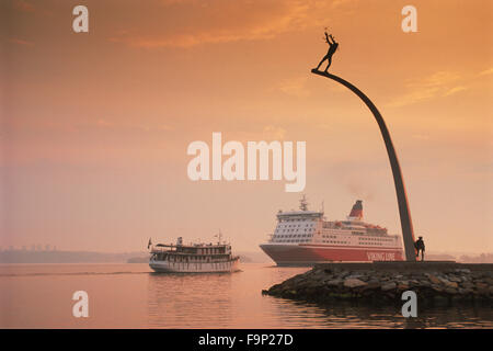 Viking Line passenger ferryboat to Finland passing Nackastrand and Carl Milles statue near Stockholm at sunrise - Stock Image