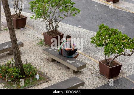 RIO DE JANEIRO, RJ , BRAZIL - December 26, 2018: A street vendor sits on a bench by the Copacabana Beach sidewalk to rest - Stock Image