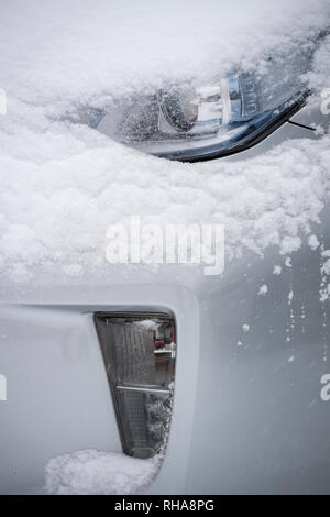 Detail of the front and headlights of a car covered in snow - Stock Image