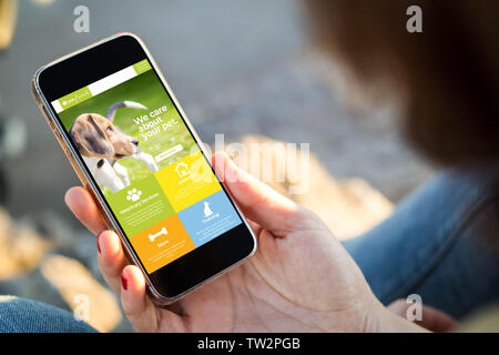 close-up view of young woman browsing pet website on her mobile phone. All screen graphics are made up. - Stock Image