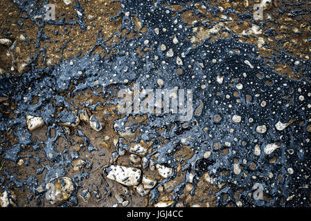 Black poured tar marks the pothole areas of a road so the holes in the old street can be repaired - Stock Image