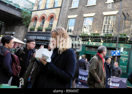 Young woman eating street food from a paper cardboard container at Borough Market in winter Southwark South London England UK Europe  KATHY DEWITT - Stock Image