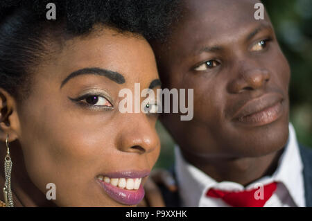 Close-up of faces of smiling young couple looking at the camera. - Stock Image