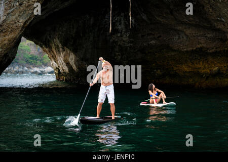 Man and woman paddleboarding, exploring caves and rock formations at sea, Los Arcos National Marine Park, Pacific - Stock Image