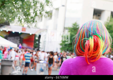 Gay Pride festival in Charlotte, North Carolina. Woman with colorful hair in the foreground. - Stock Image