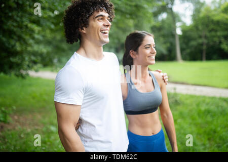 Happy young woman doing excercise outdoor in a park, jogging - Stock Image