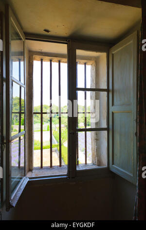 Old inward opening window with bars looking out onto garden - Stock Image