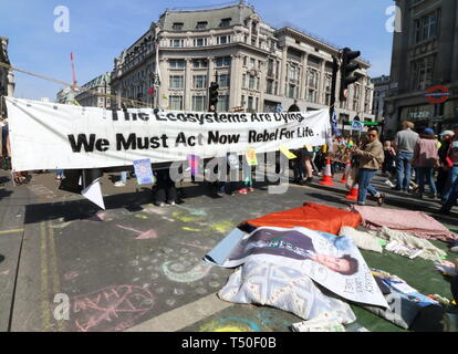 London, UK. 19th Apr, 2019. Huge banner seen across the street blocking the road during the demonstration.Environmental activists from Extinction Rebellion movement occupy London's Oxford Circus for a 5th day. Activists parked a pink boat in the middle of the busy Oxford Circus road junction blocking the streets and causing traffic chaos. Credit: Keith Mayhew/SOPA Images/ZUMA Wire/Alamy Live News - Stock Image