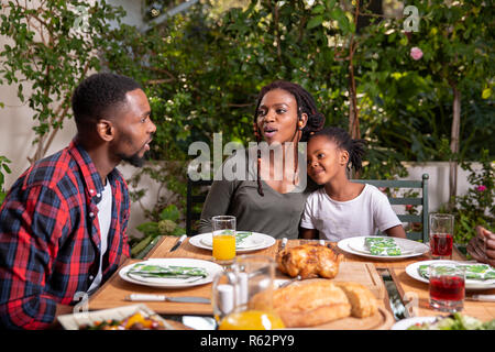 A family eating together around the table - Stock Image