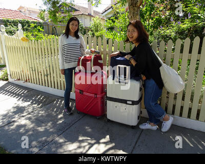 Japanese tourists Tamami Yamada and Risako Suzuki prepare to return home from Melbourne, Australia - Stock Image