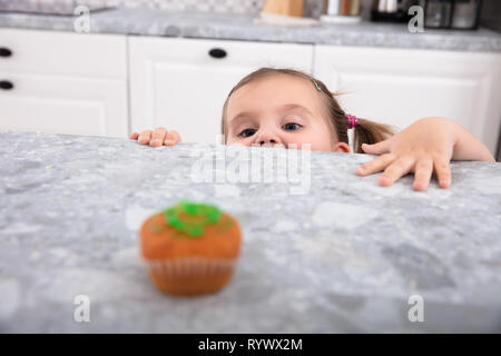 Smiling Cute Girl Looking At Cupcake On Kitchen Counter - Stock Image