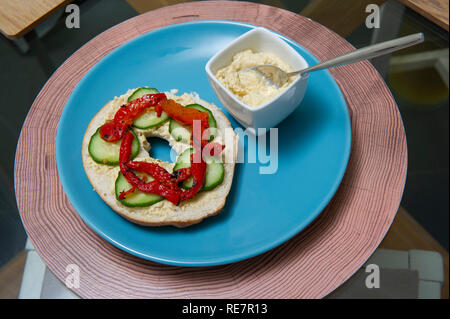 Lightly toasted Bagel with Hummus, Cucumber and chargrilled Red Peppers - Stock Image