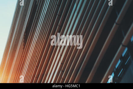 Close-up view of facade of modern building in Barcelona made by metal  stripes of varying thickness, sunny summer - Stock Image