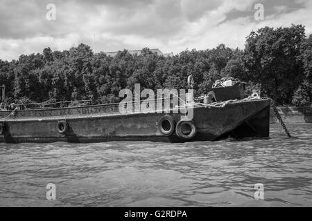 Black and white image of a rusty disused barge on the River. - Stock Image