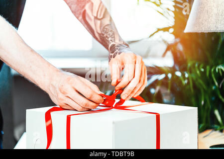 Close up of tattooed man cook ties red ribbon on white blank cake packaging. Making surprise. Hand made concept. - Stock Image