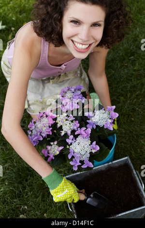 portrait of young woman working in garden - Stock Image