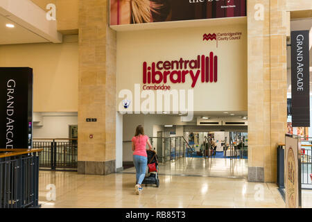 Interior of the Grand Arcade shopping centre with woman pushing buggy towards the Cambridge Central Library, Cambridge, UK - Stock Image