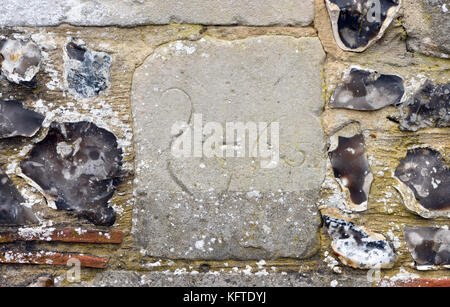 Sandstone block in a flint and sandstone wall with the date 1765 carved on it. Winchester, Hampshire, England, UK., - Stock Image